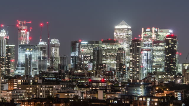 a pan across canary wharf and the isle of dogs on the skyline with residential buildings and offices in the foreground as evening arrives the city lights up - canary wharf stock videos & royalty-free footage