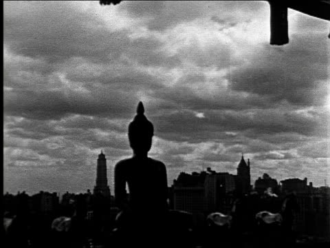 pan across central park with plaza hotel / buddha statue in silhouette with skyline and dark cloudy sky probably from burton holmes apartment on... - buddhismus stock-videos und b-roll-filmmaterial