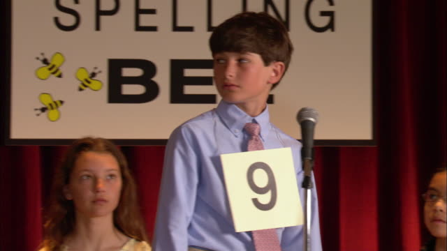 pan across children sitting on stage in spelling bee / boy walking up to microphone and spelling word / sitting down / pan across other children back to boy smiling in relief / los angeles, california - spelling stock videos & royalty-free footage