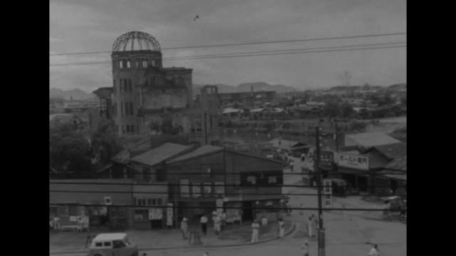 pan across city and people in streets / bell ringing at the moment the atomic bomb blasted seven years ago - 大量破壊兵器点の映像素材/bロール