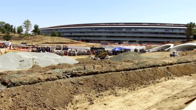 Pan across construction site outside the main building of the Apple Park known colloquially as The Spaceship the new headquarters of Apple Inc in the...