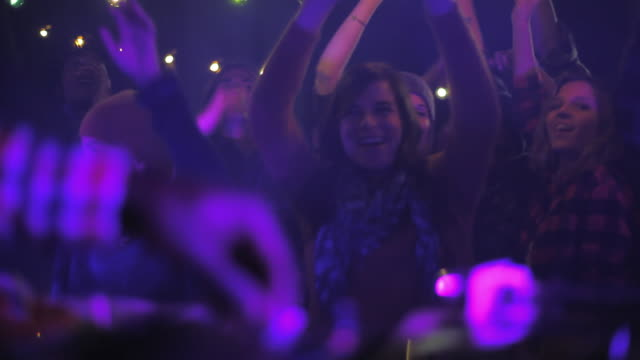 vidéos et rushes de pan across crowd dancing from behind dj's hands on crossfader of turntables - dj