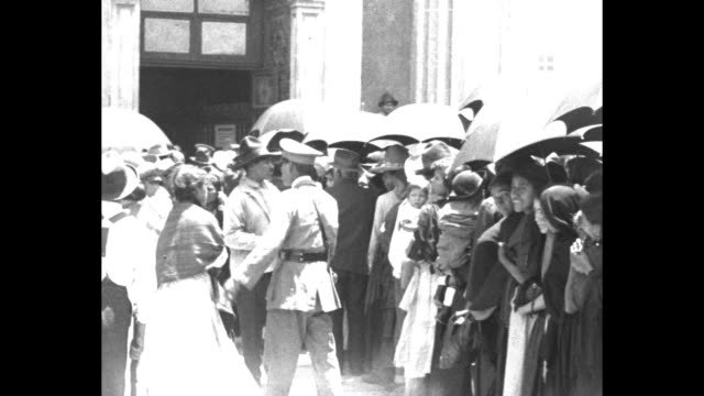 Pan across crowd milling about in front of Metropolitan Cathedral / soldier controlling people in crowd some people holding umbrellas / close panning...