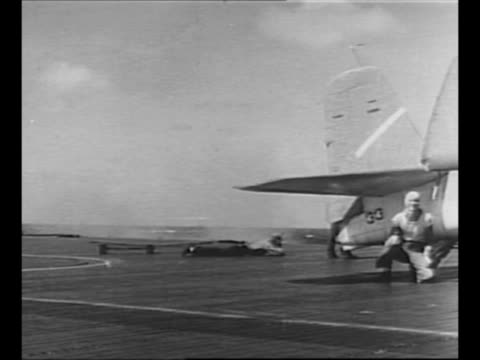 pan across deck of us aircraft carrier as japanese plane bursts into flames crashes into sea in front of carrier as tracer bullets fly above during... - military aeroplane stock videos & royalty-free footage
