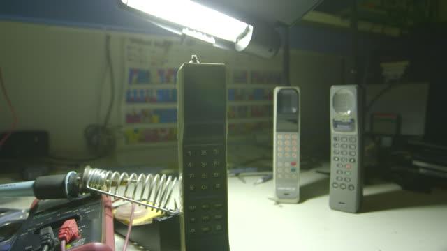 pan across early mobile phones on a work desk at home, montage - sladdlös telefon bildbanksvideor och videomaterial från bakom kulisserna