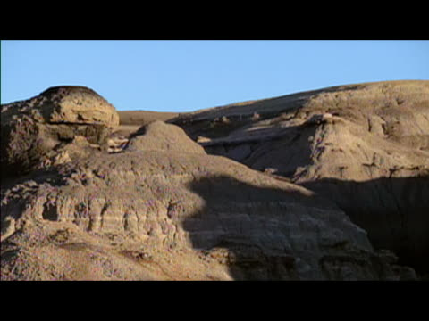 pan across eroded faces of badlands of bisti/de-na-zin wilderness area / new mexico - badlands stock videos & royalty-free footage