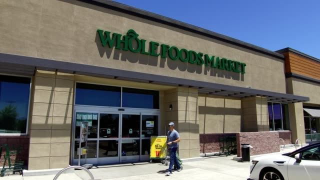 pan across facade of whole foods market grocery store in dublin california with shoppers passing by the store june 16 2017 - whole foods market stock videos and b-roll footage