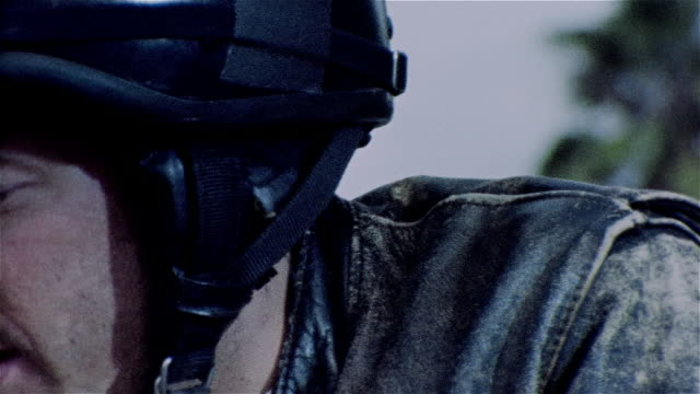 stockvideo's en b-roll-footage met pan across face of man wearing motorcycle helmet and goggles - cross processen