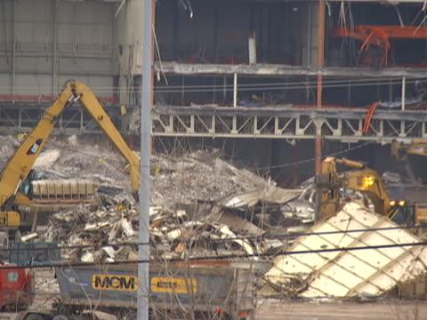 pan across factory lot with backhoe demolition - ポンティアック点の映像素材/bロール