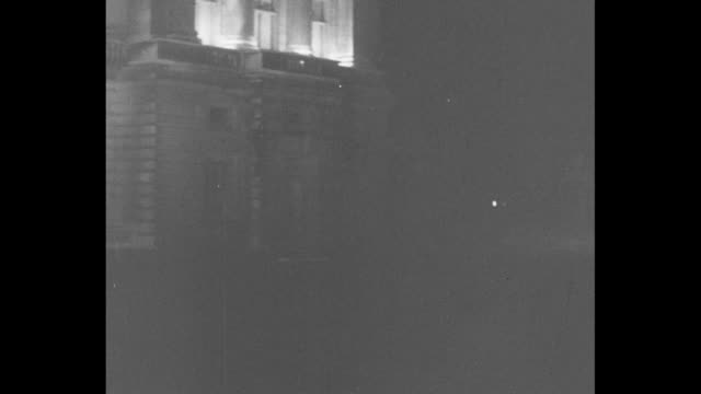 pan across floodlights lighting up darkness to palace with lighted balcony / george and mary stand on balcony / they both wave then withdraw / [note... - palace stock videos & royalty-free footage