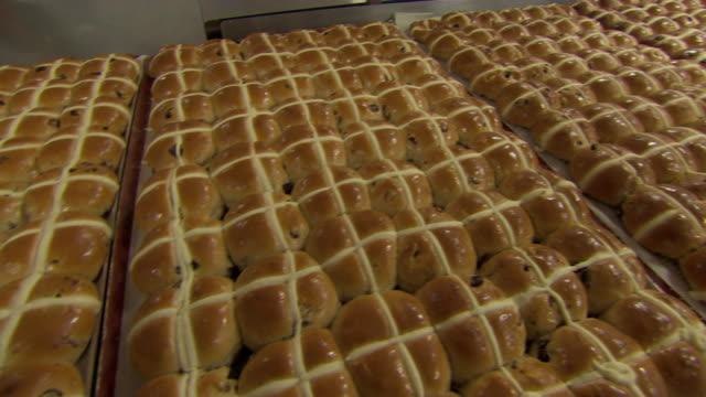 Pan across freshly-baked trays of hot cross buns in a bakery, UK.