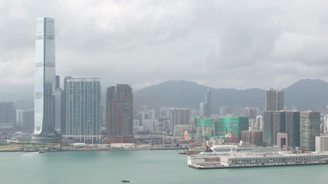 Pan across Hong Kongs Victoria Harbor looking over the Hung Hom district of the Kowloon peninsula on the right to complete the pan revealing the...
