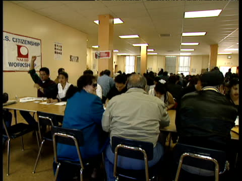 pan across immigration office with people applying for us citizenship - einwanderer stock-videos und b-roll-filmmaterial