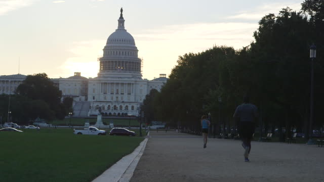 pan across joggers towards us capitol building - monument stock videos & royalty-free footage