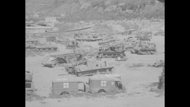 pan across large junk yard filled with debris and remains of military vehicles trucks tanks ambulances jeeps / soldiers on tractor tow damaged tank... - rimorchiare video stock e b–roll