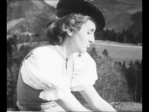 pan across legs clad in heavy white wool stockings to eva braun dressed in tyrolean costume as she sits on balcony of adolf hitler's berchtesgaden... - 1930 1939 stock videos & royalty-free footage