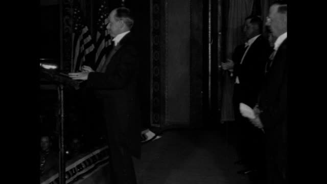 Pan across line of people including famed aviator Charles Lindbergh and wife Anne next to him standing on porch of White House / Pres Calvin Coolidge...
