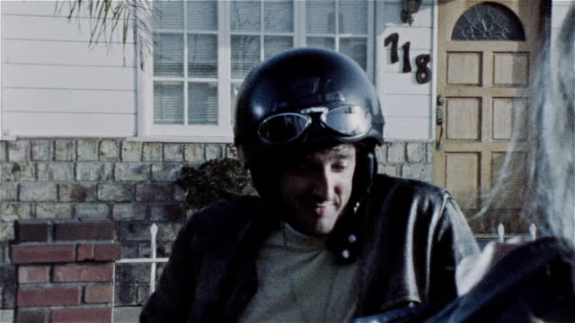pan across man in motorcycle helmet smirking then looking upset during conversation with woman facing him - smirking stock videos and b-roll footage