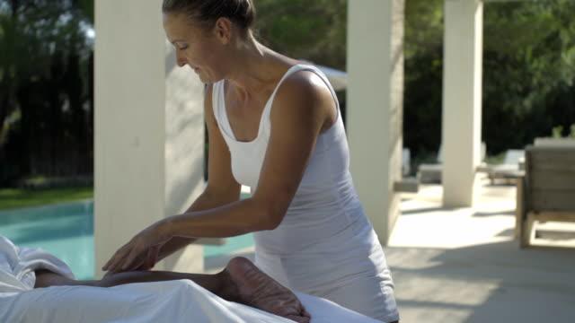 pan across mature female client receiving a massage - masseur stock videos & royalty-free footage