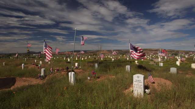 pan across military cemetery and american flags in new mexico, wide shot - südwestliche bundesstaaten der usa stock-videos und b-roll-filmmaterial