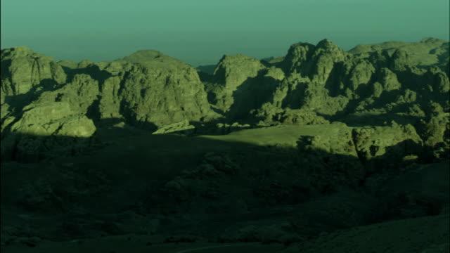 pan across mountains with peaks sunlit and base in shadow, near petra, jordan - アラバ砂漠点の映像素材/bロール
