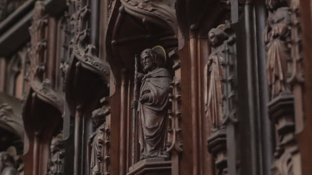 pan across ornamental wooden carvings depicting the life of st laurence in st laurence's church in ludlow in shropshire, uk. - pregare video stock e b–roll