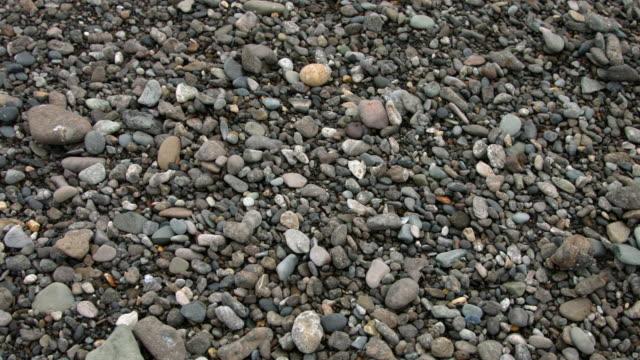Pan across pebbles on a beach.