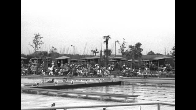 pan across pool where diving competition is held spectators line poolside in folding chairs / diver pat mccormick and two other winners hold patches... - textile patch stock videos & royalty-free footage
