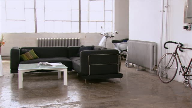 pan across potted palm, road bike, sofa, coffee table, vase, and scooter by window in loft space - 屋根裏部屋点の映像素材/bロール