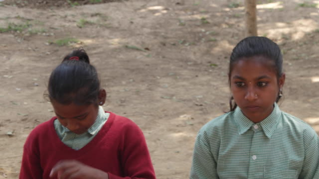 Pan across primary school students looking pensive and having their lunch during a break