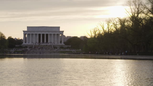 vidéos et rushes de pan across reflecting pool to lincoln memorial during sunset - lincoln memorial