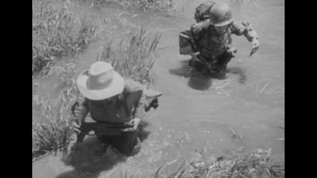 / pan across rice paddy to village and french soldiers standing around trucks parked on road near ninh binh where lieutenant bernard de lattre de... - indocina video stock e b–roll