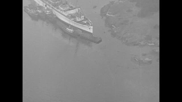 pan across rms empress of canada sitting on rocks / aerial shot of empress sitting on rocks with boats next to her / people standing on shore looking... - 客船点の映像素材/bロール