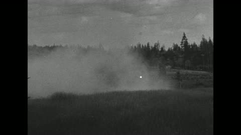 pan across road and forest filled with smoke / smoke floating from bank of river onto river / soldiers dragging boats down slope towards water /... - moving up点の映像素材/bロール