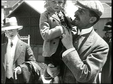 pan across row of young adults and children in feathered hats smiling at camera / burton holmes holding young blonde child wearing lederhosen and... - 1910 stock videos & royalty-free footage