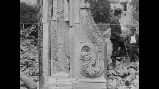 pan across ruins with villagers among rubble from mt. stromboli eruption / pan refugees in front of belongings and among makeshift tents, woman... - 1920 video stock e b–roll