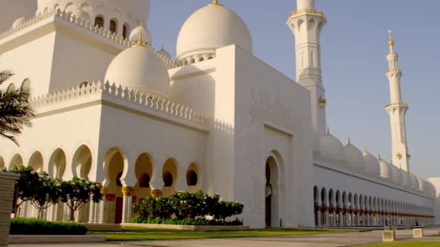 pan across sheik zayed grand mosque, abu dhabi, at golden hour - grand mosque stock videos and b-roll footage