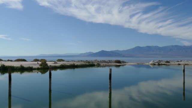 4k pan across small bay on the shore of the salton sea wispy clouds reflecting in the calm blue water - インペリアルバレー点の映像素材/bロール