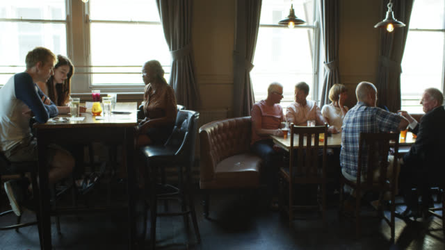 pan across tables in crowded pub - yorkshire england stock videos & royalty-free footage