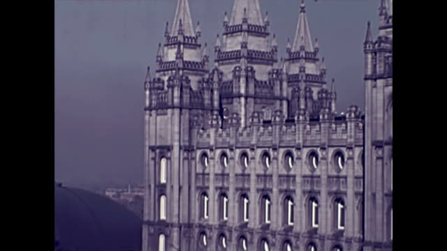 pan across temple square to the salt lake city temple / houses / cars driving through eagle gate / pan left to hotel utah - 1937 stock videos and b-roll footage