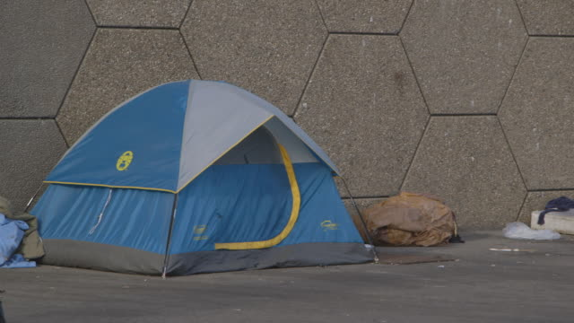 vídeos y material grabado en eventos de stock de pan across tents and bed in homeless sanctuary, couple walks by, wide shot - tienda de campaña