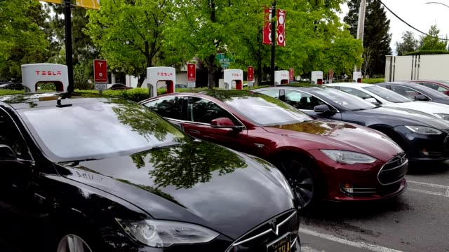 pan across tesla motors sedans plugged in and charging at a supercharger station in the silicon valley town of mountain view california april 9 2017 - limousine stock-videos und b-roll-filmmaterial
