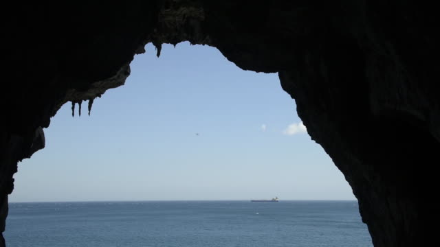 Pan across the entrance of Gorham's Cave at the base of the Rock of Gibraltar.