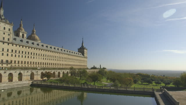 Pan across the exterior of the grand El Escorial palace at San Lorenzo de El Escorial, Spain.