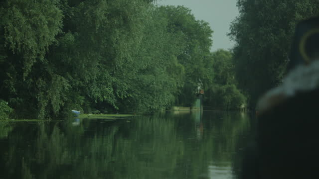 pan across the flat, calm river cam onto the porthole of a small, weathered old boat on an idyllic summer's day, cambridge, uk. - flussufer stock-videos und b-roll-filmmaterial