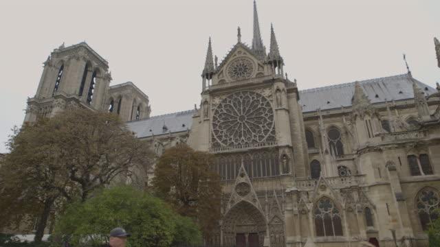 pan across the imposing south side of notre dame de paris, france. - notre dame de paris stock videos & royalty-free footage