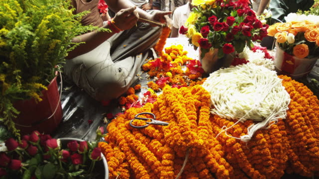 Pan across the preparation of a garland of marigolds in Guwahati in Assam, India.