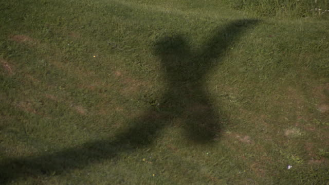 Pan across the shadow of a cross-shaped First World War memorial in the Somme region, France.