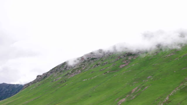 stockvideo's en b-roll-footage met a pan across the vast meadows of an alpine valley near the satsar army post of the indian army, with the indian 'tricolour' flag fluttering - indiase leger