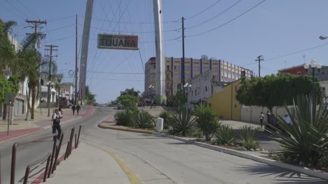 pan across tijuana welcome sign, wide shot - tijuana stock videos & royalty-free footage